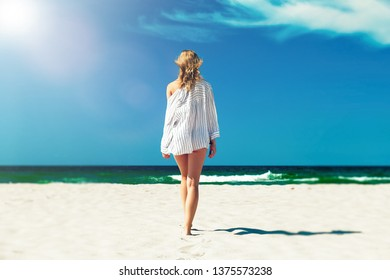 sad single young woman in white blouse walking on sand sea beach with blue sky and sun flare