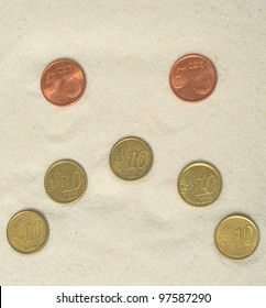 Sad smiley made of euro coins on the sand