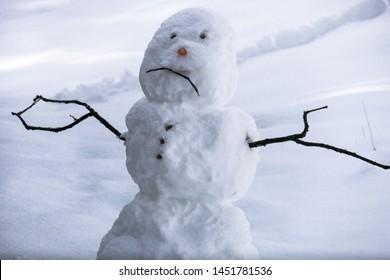 Sad snowman frowning in Sierra winter snow - California