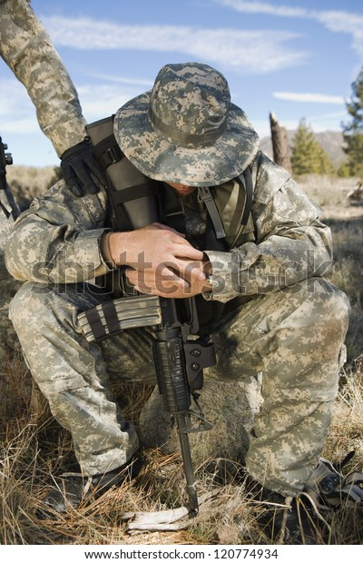 Sad solider sitting with a gun