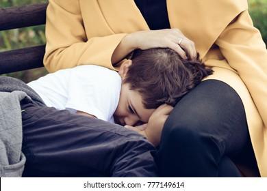 Trauriger Sohn, der auf dem Schoß der Mutter tröstet. Schüchterner kleiner Junge, der sich in der Umarmung der Mutter versteckt.