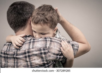 sad son hugging his dad near wall at the day time