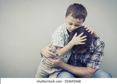 sad son hugging his dad near wall of house at the day time
