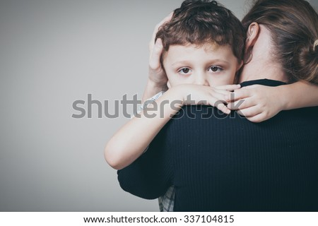 sad son hugging his mother at home. Concept of couple family is in sorrow.