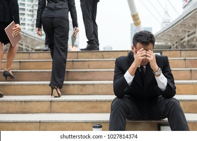 Sad or stress Business man sit on stair while other Business guys walk upstair. Head down with feeling bad covered face by two hands. Unsuccessful vs. successful businessmen. working competition.