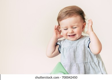 Sad stressed baby with her hands over ears, not listening