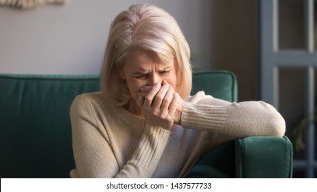 Sad stressed old middle aged woman widow mourning crying alone sit on couch at home, upset desperate senior mature elder grandma grieving weeping suffering from anxiety grief sorrow disease concept