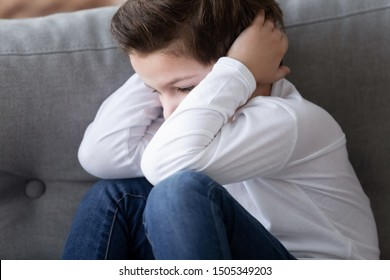 Sad stressed stubborn little cute kid boy sit alone hiding feel scared upset lonely abused, preschool child close ears not listening suffer from earache showing rebellious naughty behavior concept