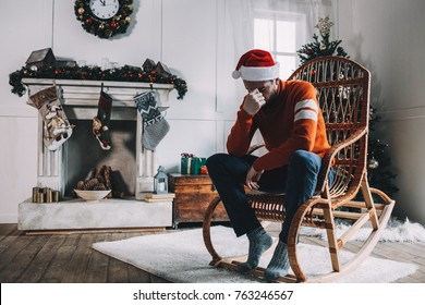 Sad and stressed young man is sitting at the edge of a rocking chair near big decorated fireplace and holding his hand near the face. This guy looks tired, bored and unhappy at the same time.