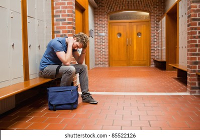 Sad student sitting on a bench in a corridor