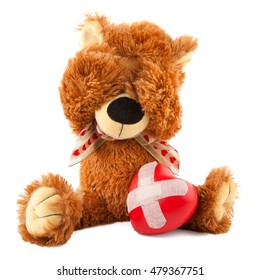 Sad teddy bear with broken heart on white