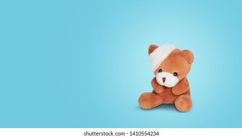 Sad teddy bear doll with bandage sitting alone on blue background. Child injuries, injury treatment concept