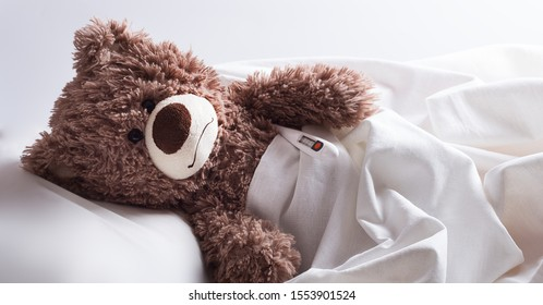 Sad teddy bear lies in bed with a thermometer. Toy closeup. The child remained at home due to illness