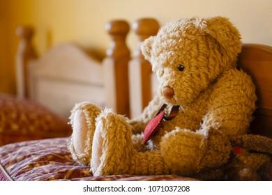 Sad teddy bear on a bed