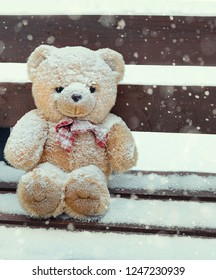 sad teddy bear in winter, lost and forgotten. Teddy bear alone on snow during winter time. Brown bear toy covered snowflake, soft toy lost on the bench.