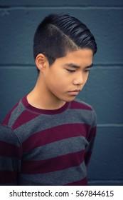 Sad teen Asian boy looking downward, arms held behind his back.