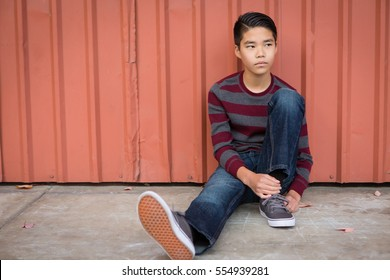 Sad teen Asian boy sitting against a wall looking pensive and off to the left.