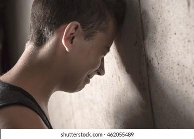 Sad teen boy concrete