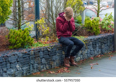 Sad teen boy crying outdoor after bad date gone wrong, covering face with hands doesn't know what to do or feel, just weeping about unfortunate accident sitting alone on the wall on city street park