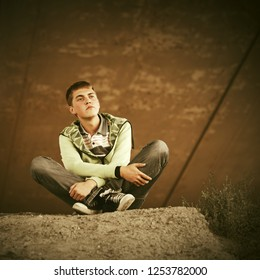 Sad teen boy in depression sitting on the ground outdoor Stylish trendy male model wearing light green hoodie and gray jeans