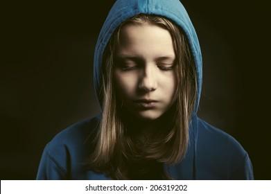 Sad teen girl in hood sitting with closed eyes