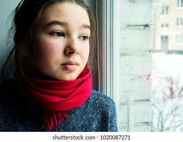 Sad teen girl looks out the window