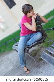 sad teen girl on the park bench