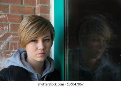 Sad teen girl outside school, with reflection from door window