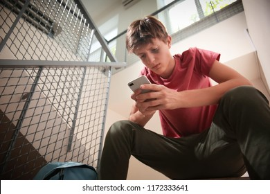 Sad teenage boy with mobile phone sitting on stairs. Bullying at school