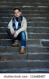 sad teenage boy sit on stone stairs outdoor