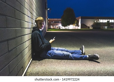 Sad teenage boy sitting on the ground against a brick wall at night. He is listening to music through a pair of headphones.