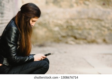 Sad teenage girl feeling lonely, looking at smartphone reading message.