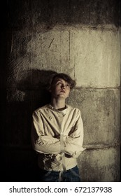 Sad teenage male child looking up toward grungy concrete wall while tied in straight jacket. Includes copy space.