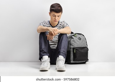 Sad teenage student sitting on the floor and leaning against a gray wall
