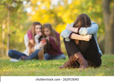 Sad teenage woman sitting with head down near laughing group