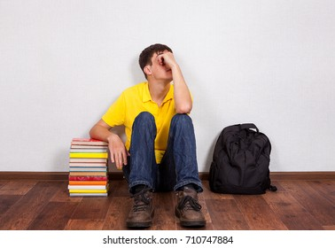 Sad Teenager with a Books on the Floor by the Wall