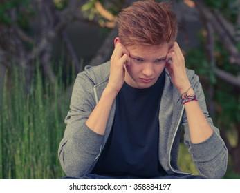 Sad teenager boy outdoors