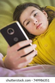 Sad teenager girl in bed with smartphone