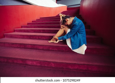 Sad teenager girl depressed sitting on stairs, loneliness scene minimal style.