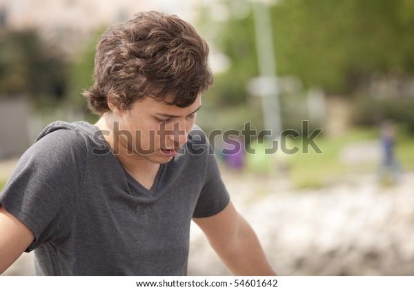 sad teenager looking down in outdoor