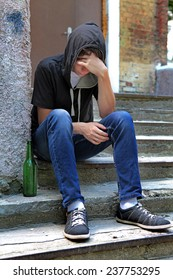 Sad Teenager on the landing steps with a Bottle of the Beer