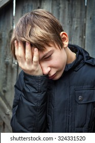 Sad Teenager on the Wooden Wall Background