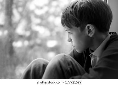 Sad teenager sitting on window, black-and-white photo