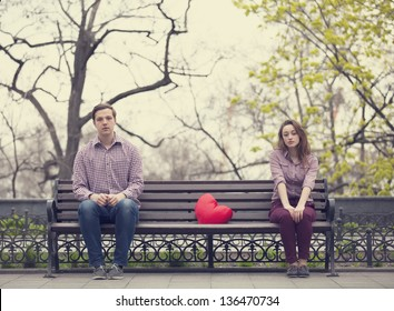 Sad teens sitting at the bench at the park