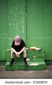 Sad tennis player having rest in front of old training wall