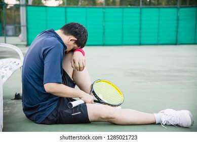 Sad tennis player sitting in the court after lose a match - people in sport tennis game concept