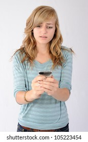 Sad Text Message Received. Teenage girl reacting to a sad text message received on her smartphone. Note: Not Isolated.