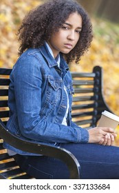Sad thoughtful or depressed mixed race African American girl teenager female young woman drinking takeaway coffee outside sitting on a park bench in autumn or fall
