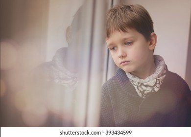 Sad thoughtful little boy looking through the window. Rainy day