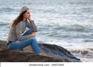 Sad and thoughtful woman sitting by the water deep in thought.